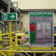 Vluchtwegsignalering in lijn met het ontruimingsplan in een industriele omgeving.