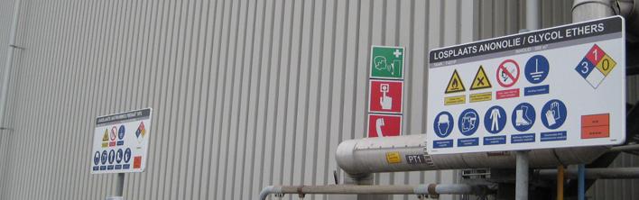 Een bord bij een verlaadplaats van chemicalien met veiligheidssymbolen.