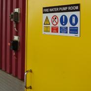 Een veiligheidszonebord met veiligheidssymbolsen en tekst op een schuifdeur van een offshore platform.