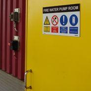 A bespoke safety sign with safety symbols and text on a sliding door of an offshore platform.