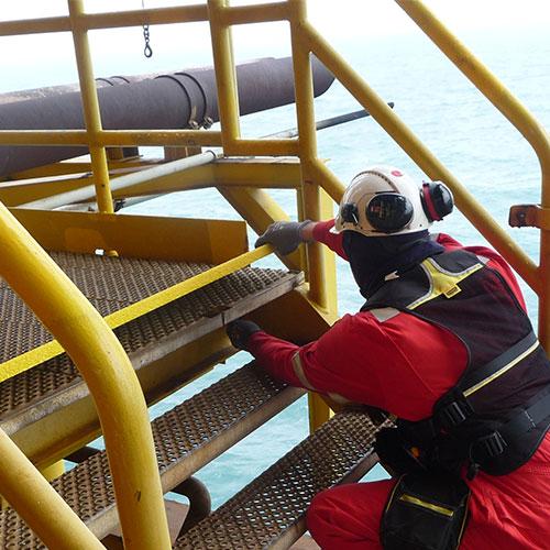 Blomsma monteur bevestigt anti-slip trapneuzen en hand aan leuning panelen op een offshore platform