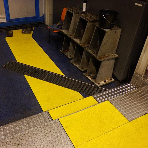 Anti-slip looppad panelen toegepast op een korte trap met contrasterend geel en zwart materiaal.