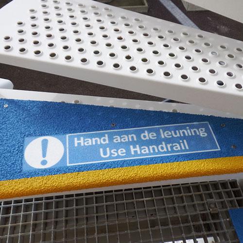 Door hand aan leuning panelen te plaatsen op de bovenste en onderste trede van een trap, worden bezoekers en medewerkers gewaarschuwd.