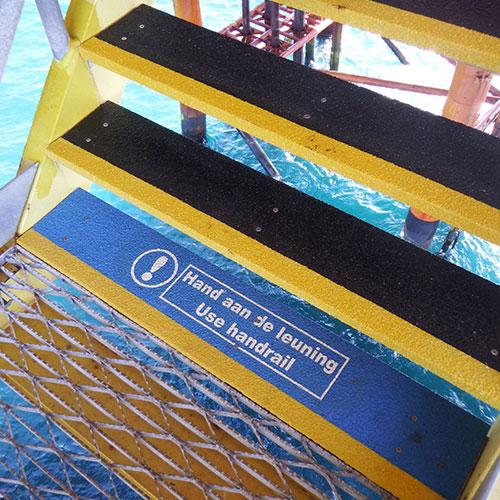 Belangrijke anti-slip veiligheidsboodschap om medewerkers te behoeden, geplaatst op onderste en bovenste trede van de trap