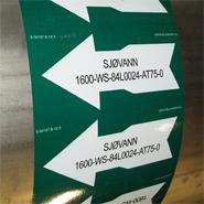 Een leidingmarkering met mediumbenaming en lijn nummer conform NORSOK richtlijnen voor de Noorse offshore industrie.
