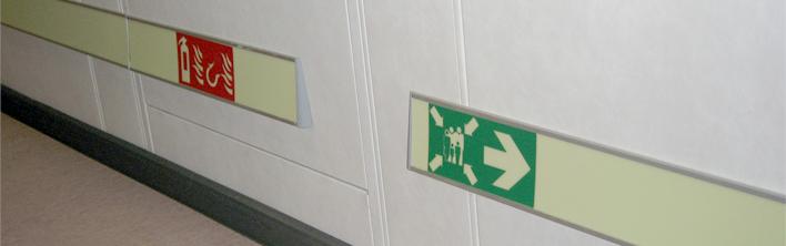 Veiligheidssymbolen geintegreerd in een nalichtend vluchtroutegeleidingssysteem.