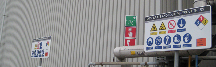 A bespoke sign at a chemical handling point with safety symbols.